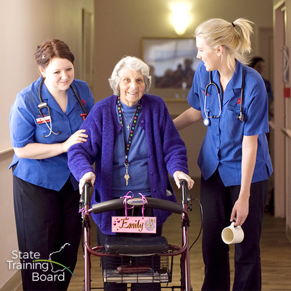 Two female aged care workers, with a resident in an aged care home.