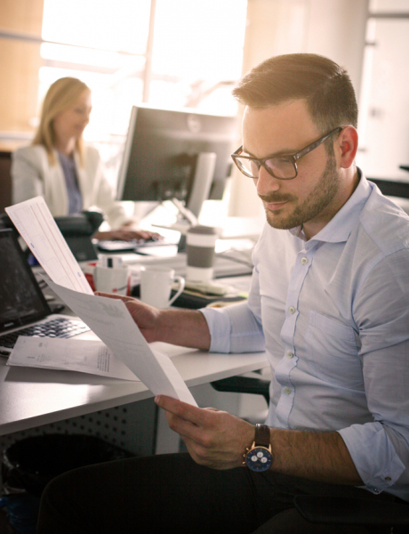 A male business man looking at a contract document.
